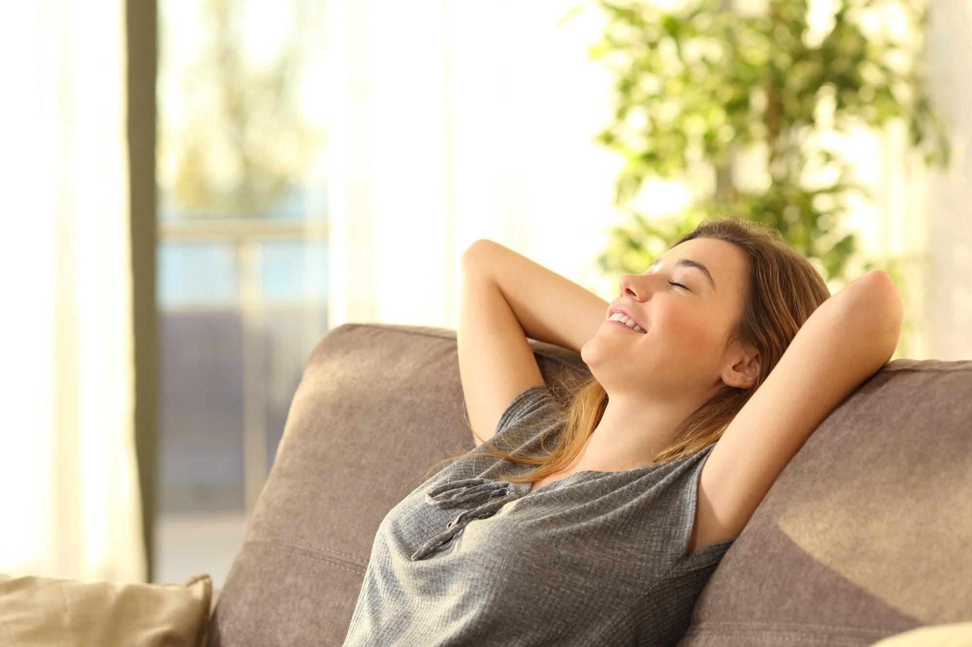 Donna felice che riposa su un divano di una Casa Passiva - Mac Costruzioni Generali